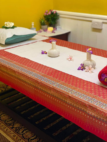 Traditional Thai massage surface on the floor, decorated with rolled towels
