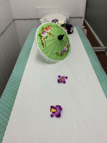 Massage table in white with flowers and rolled towels